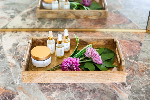 Image of Tray with Aimee Raupp Beauty products and flowers