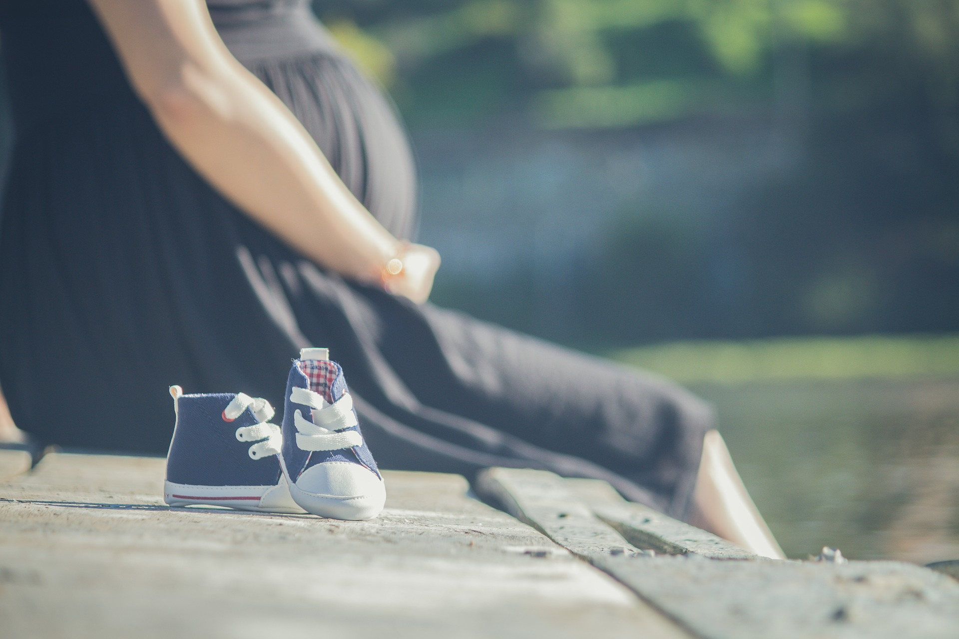 pregnant woman sitting next to baby shoes